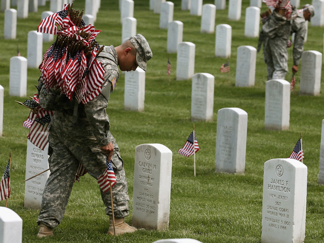 """Soldiers from the 3d U.S. Infantry Regiment (The Old Guard) place flags in front of the gravesites in Arlington National Cemetary, Va., May 22, 2014, during """"Flags In"""".  U.S. Army photo by Klinton Smith."""